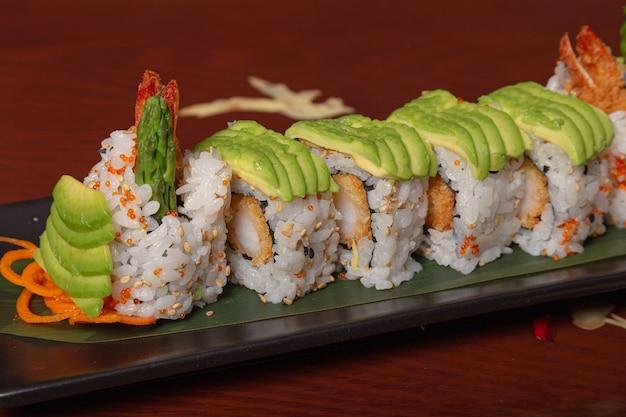 木製のテーブルにアボカド、海老の天ぷら、チーズを巻いたサーモン寿司のグリル。孤立した画像 Premium写真