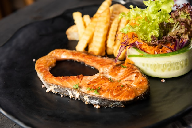 Grilled salmon with french fries and salad Free Photo