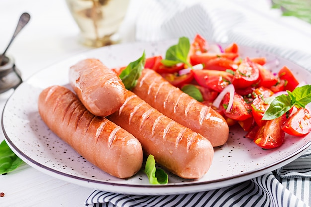 Grilled sausage with tomatoes, basil and red onions Free Photo
