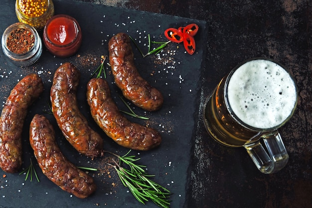 Grilled sausages on a dark stone board with a glass of beer Premium Photo