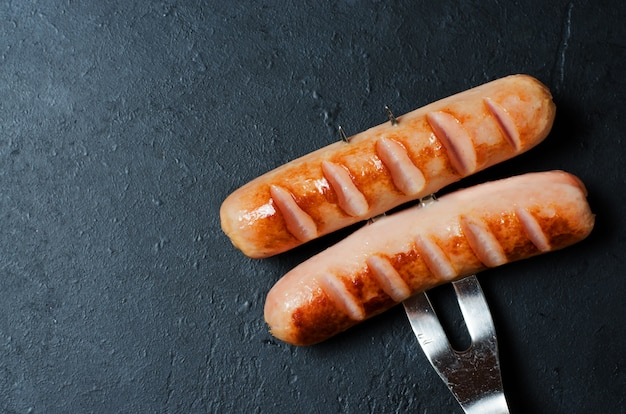 Grilled sausages fried on a metal fork. unhealthy diet. Premium Photo