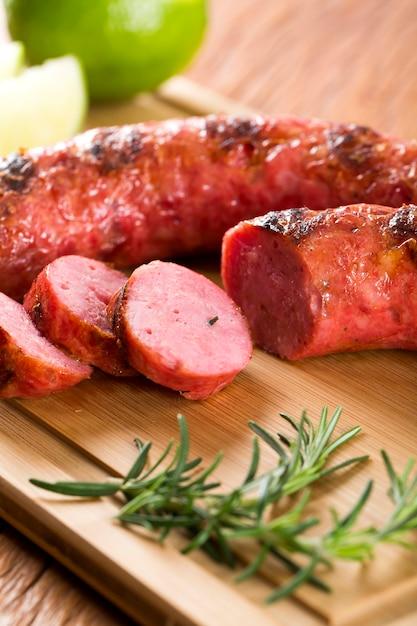 Колбаски гриль на мангале на доске с лимоном, картошкой и помидорами Premium Фотографии