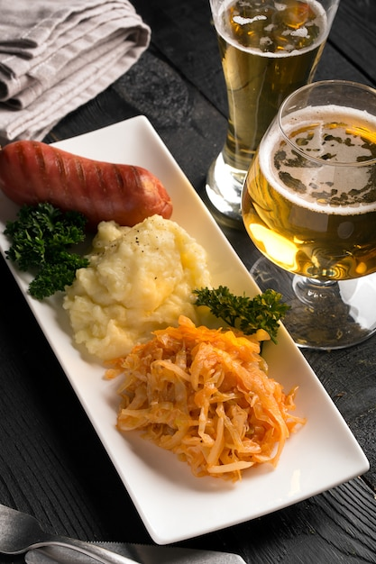 Grilled sausages and potatoes with glass of beer Premium Photo