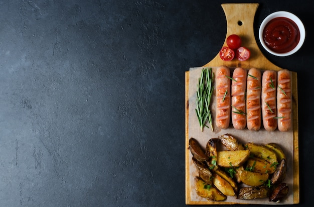Grilled sausages on a wooden chopping board. fried potatoes, rosemary, tomatoes, tomato ketchup. unhealthy diet. Premium Photo