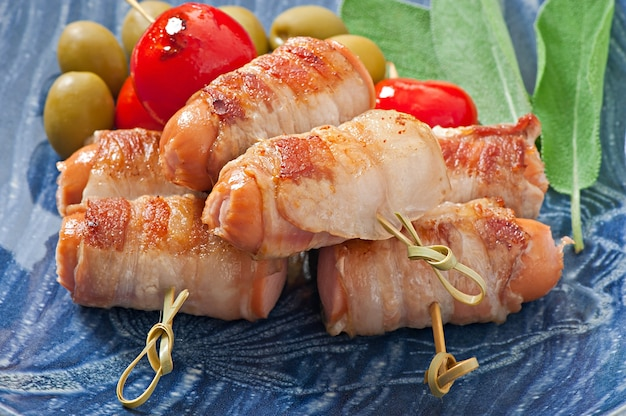 Grilled sausages wrapped in strips of bacon with tomatoes and sage leaves Free Photo