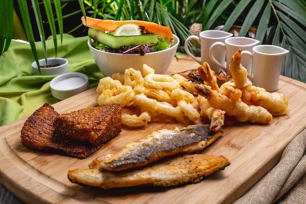 木の板に魚介類のグリル魚エビカラマリーグリーンサラダ側面図 無料写真
