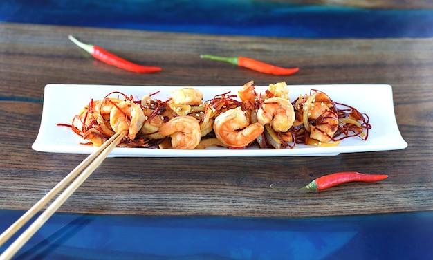 양파와 칠리 흰 접시에 구운 새우 프리미엄 사진