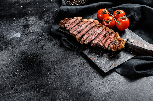 Grilled sliced strip loin steak on a meat cleaver. black background. top view. copy space Premium Photo