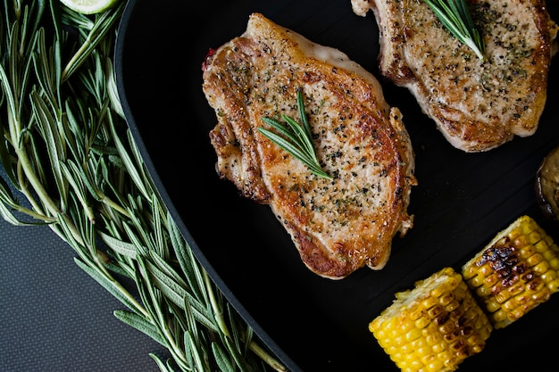 Grilled steak with vegetables in a pan decorated with rosemary. Premium Photo