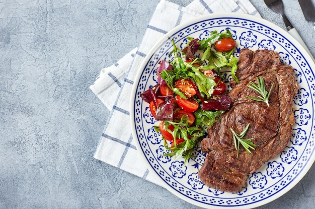 Grilled steaks and vegetable salad. table setting, food concept. top view Premium Photo