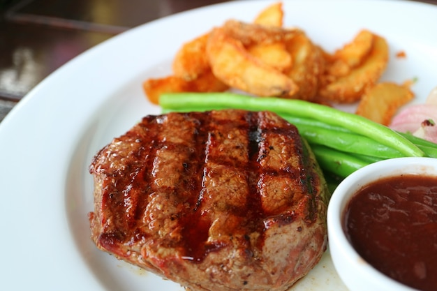 Grilled tenderloin steak with blurred steamed vegetables and fried potatoes in background Premium Photo