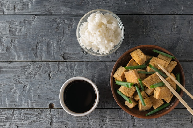 Grilled tofu cheese with green onions, rice and soy sauce on a wooden table. grilled cheese appetizer. flat lay. Premium Photo