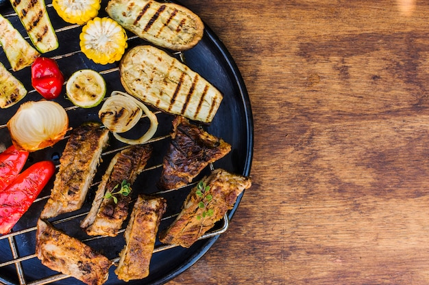 Grilled vegetables and meat in grill on table Free Photo