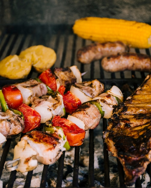 Grilled vegetables and sausages on hot grill charcoal Free Photo