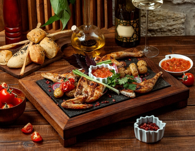Grilled whole chicken served with tomato sauce on stone board Free Photo