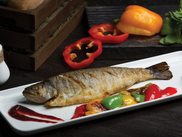 Grilled whole fish served with grilled bell peppers Free Photo