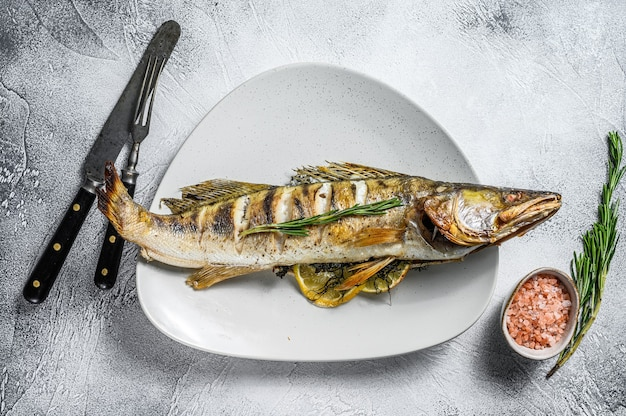 Premium Photo Grilled Zander Walleye Fish With Herbs And Lemon On A Plate Gray Wooden Background Top View