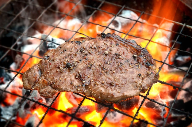 Grilling pepper steaks on flaming Premium Photo