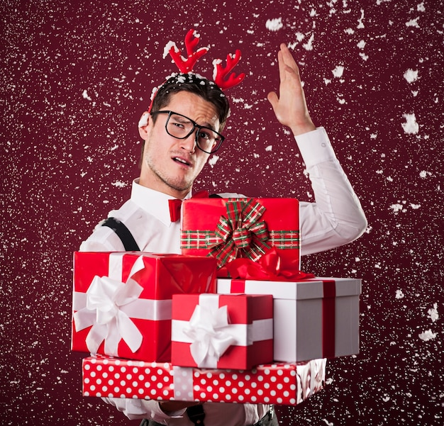 Grimacing man with stack of christmas presents Free Photo