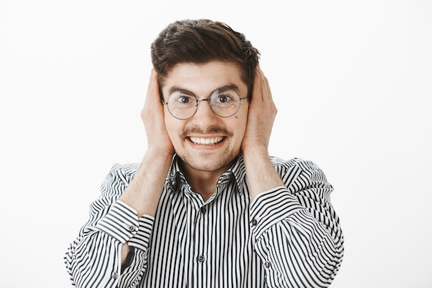 Ghignando eccitato maschio attraente con gli occhiali, che copre le orecchie con i palmi delle mani e sorride ampiamente, in attesa del forte rumore di fuochi d'artificio o scoppio, compiaciuto e felice durante la festa sul muro grigio Foto Gratuite