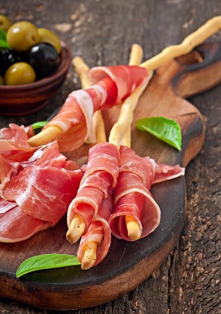 Grissini bread sticks with ham, olives, basil on old wood Free Photo