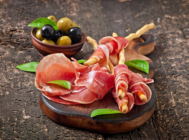 Grissini bread sticks with ham, olives, basil on old wooden Free Photo
