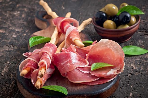 Grissini хлебные палочки с ветчиной, маслинами, базиликом на старых деревянных Бесплатные Фотографии