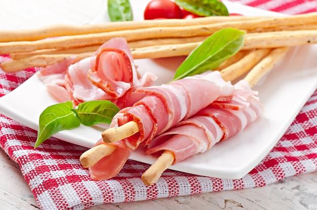 Grissini bread sticks with ham, tomato and basil Free Photo