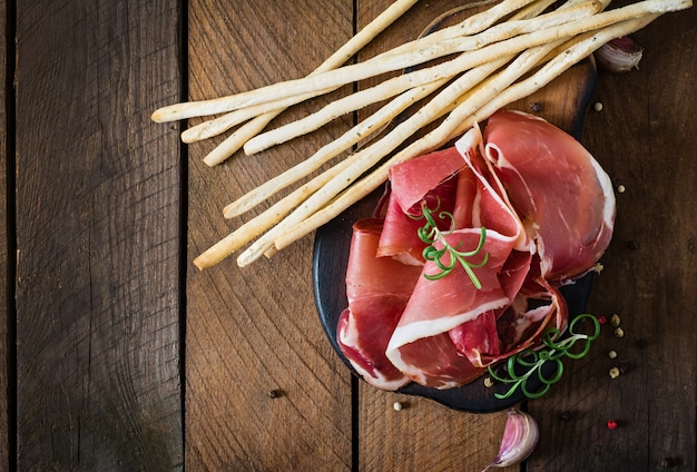 Grissini bread sticks with prosciutto Free Photo