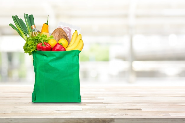 Groceries in green reusable shopping bag on wood table Premium Photo