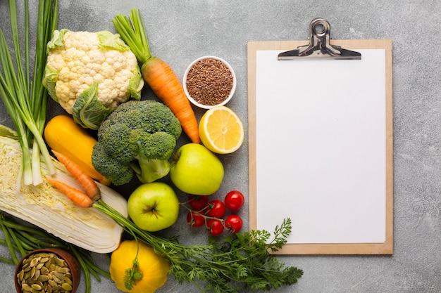スレートの背景にクリップボードと食料品 Premium写真