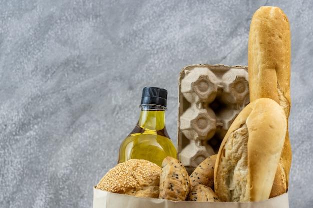 Продуктовый мешок с маслом для жарки яиц и разнообразным хлебом в одноразовом бумажном пакете на сером винтажном фоне чердака. пекарня, еда и напитки, и концепция бакалеи для доставки. Premium Фотографии
