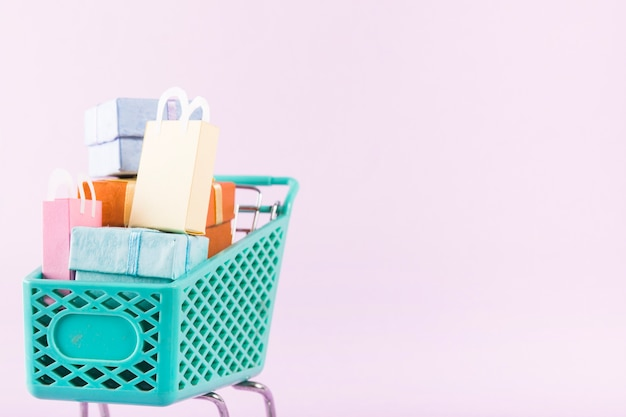 Grocery cart with colourful gift boxes and shopping bags Free Photo