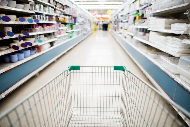 Grocery shopping cart in supermarket aisle Free Photo