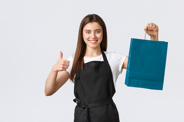 Grocery store employees, small business and coffee shops concept. friendly cute saleswoman packing your gift or purchased items in paper bag, showing thumbs-up and smiling Premium Photo