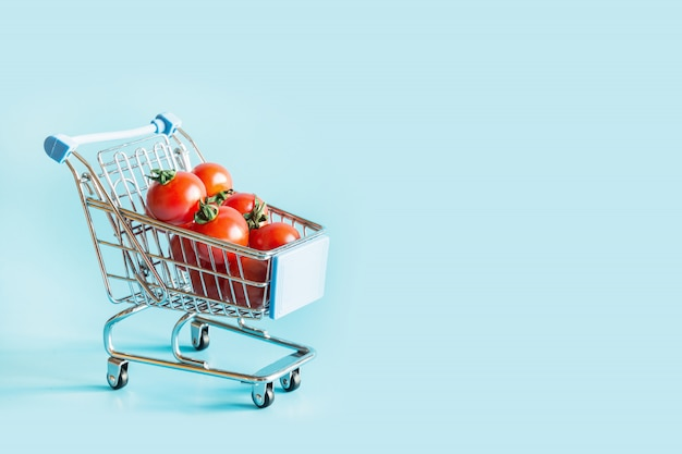 Grocery trolley with tomatoes on blue. Premium Photo