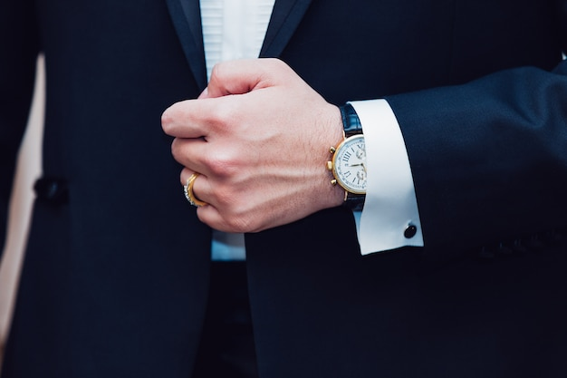 Groom adjusts a button on his jacket Premium Photo
