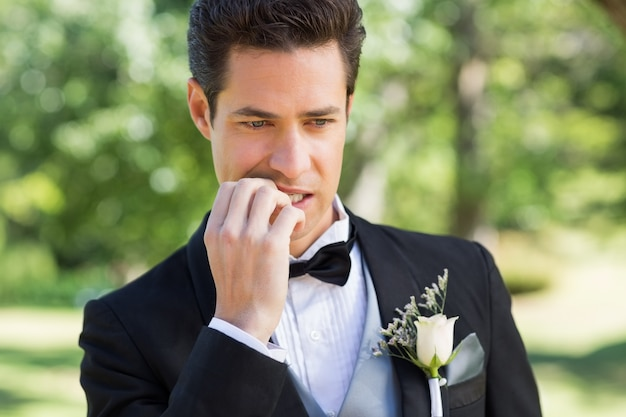Groom biting nails in garden Premium Photo