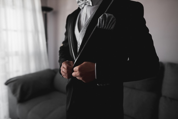 Groom in black tuxedo and gray bow tie correctly putting on his jacket buttons Premium Photo