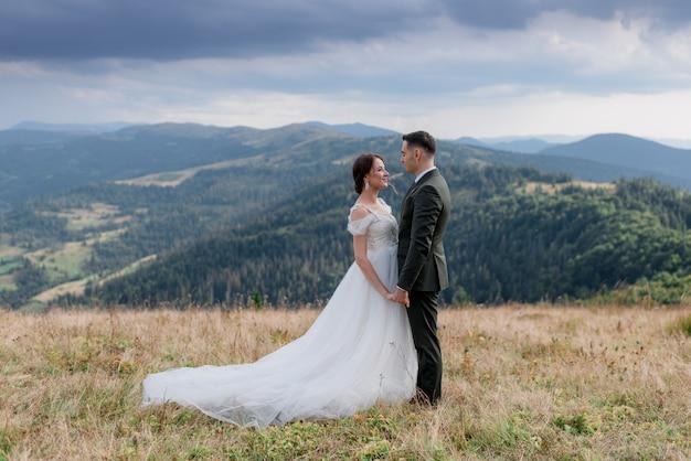 Lo sposo e la sposa sono in piedi uno di fronte all'altro sulla cima di una collina tra le montagne estive Foto Gratuite