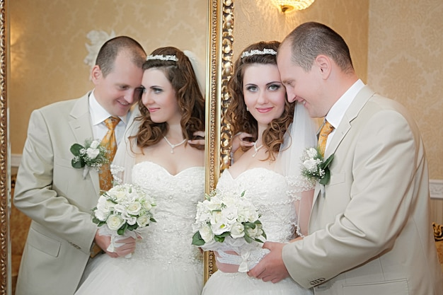 Groom and the bride stand near a mirror with a gold frame and are reflected in it Premium Photo