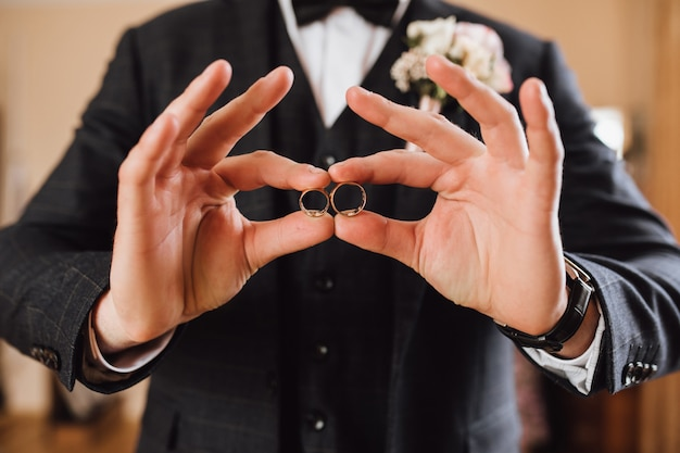 Groom demonstrates two wedding rings, without face Free Photo