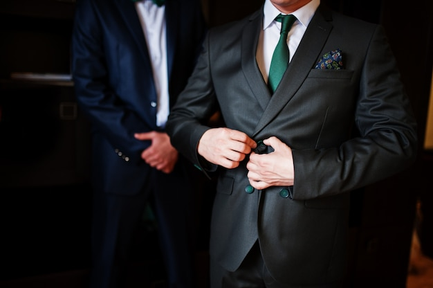 Groom dressing up in the presence of his groomsmen in the room. Premium Photo
