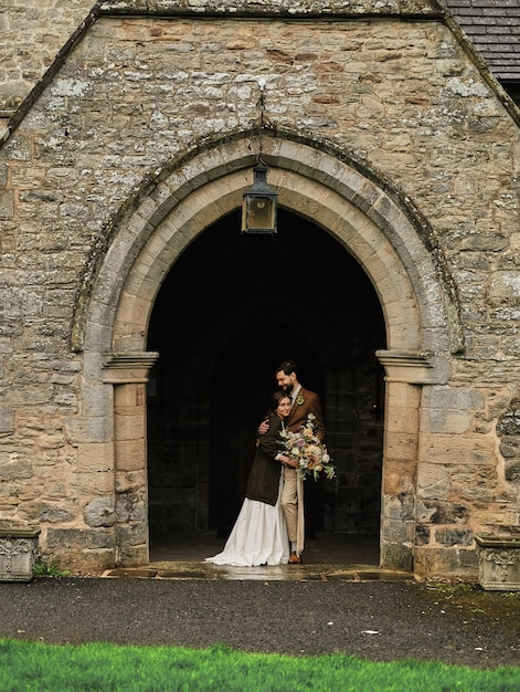 The groom embraces the bride near the old english church, cloudy day. Premium Photo