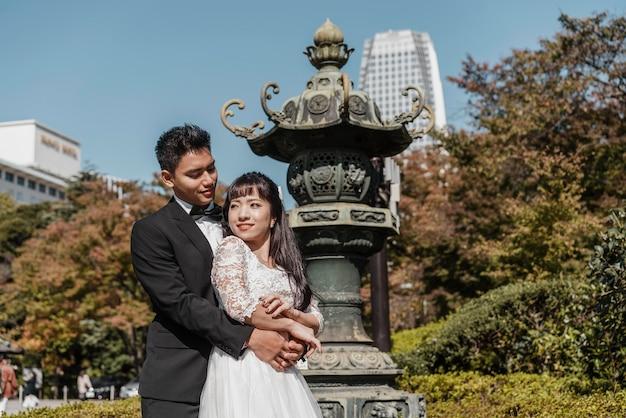 Sposo che abbraccia la sposa all'aperto Foto Gratuite