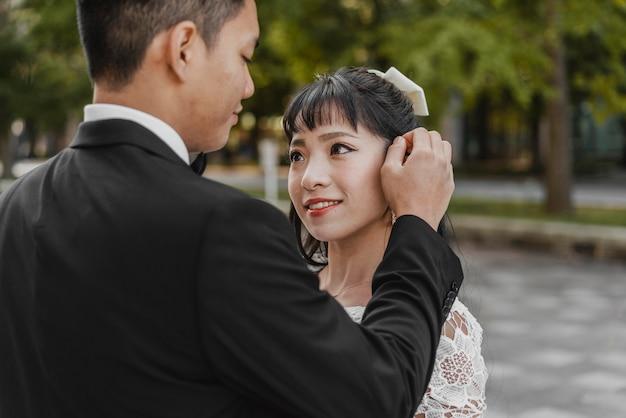 Sposo che fissa i capelli della sposa all'aperto Foto Gratuite