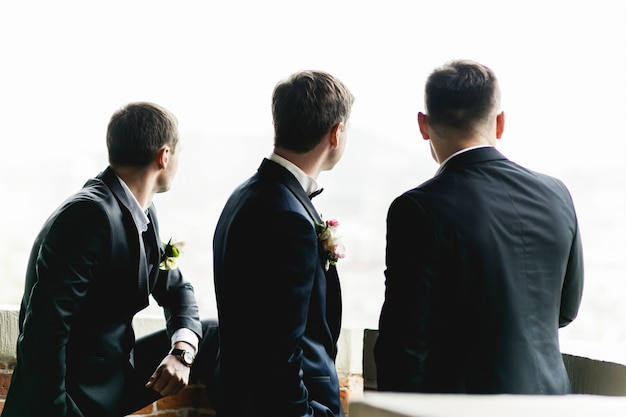 Groom and groomsmen stand on the balcony Free Photo