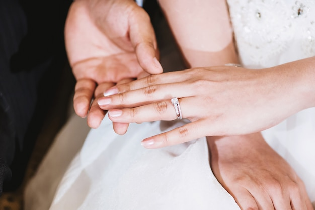 The groom holding the bride hand after put the wedding ring on her finger Premium Photo