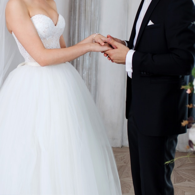 The groom holds the bride's hand, wedding vows. Premium Photo