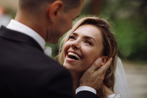 Groom holds bride tender in his arms while she looks at him Free Photo